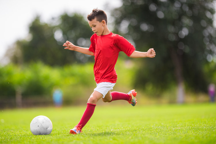 A boy kicks a soccer ball.