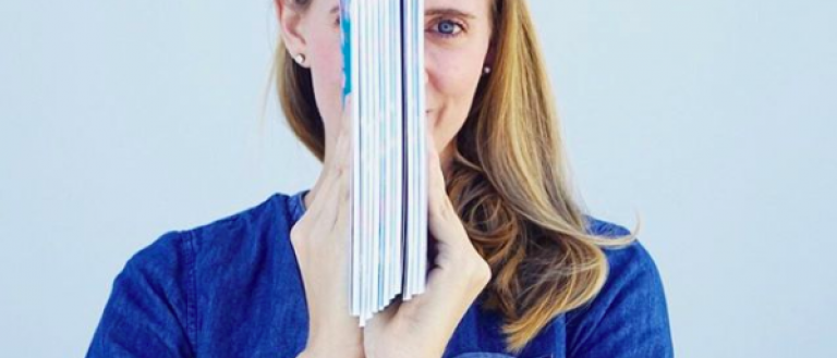 Image Description: Kathryn faces the camera, wearing a blue shirt and a smile. In front of her face, however, she holds her book (from the side) so that it obscures half her face.
