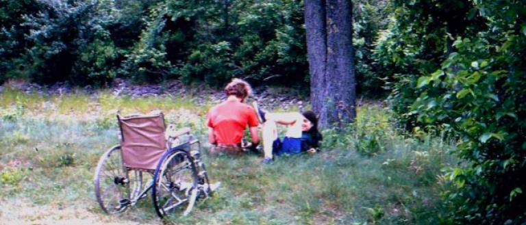 In this faded picture from the 1970s, we see two people sitting by a tree in a grassy field. Behind them is a wheelchair.