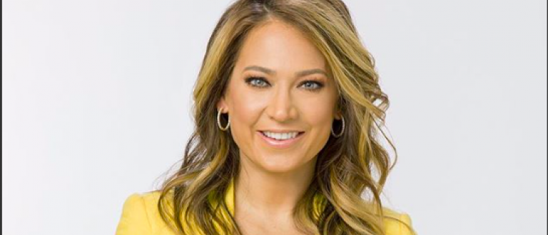 Image Description: A photo of Ginger Zee. Ginger smiles at the camera, with her arms folded across her chest. She wears a yellow suit jacket.