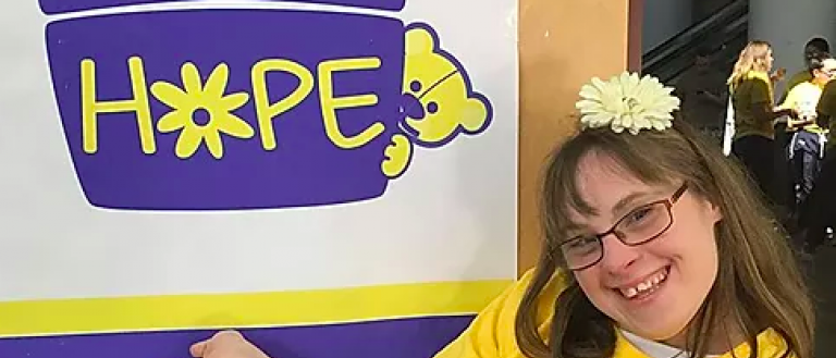 Image Description: Brittany Schiavone poses with the Brittany's Baskets of Hope logo. She wears a yellow t-shirt and has a white flower in her hair.
