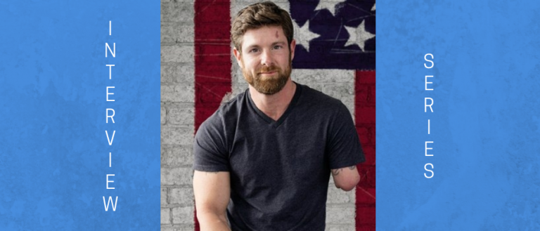 Image of a solider who is amputee from combat. His name is Noah Galloway. He is sitting in a dark gray t-shirt, smiling at the camera, in front of an American flag hanging horizontally.