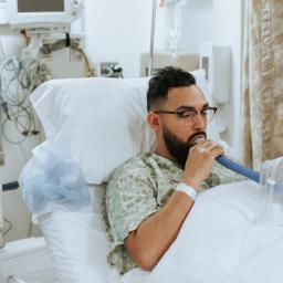 A man in a hospital bed, blowing into a lung function test.