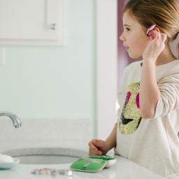 Image Description: a young girl fits her hearing aid into her ear while standing in front of her sink mirror.