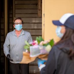 Image Description: A man, wearing a mask and gloves, receives a flower delivery from a woman also wearing a mask and gloves.