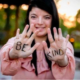 "Image Description: Rena Rosa holds up her hands to the camera. Written on them are the words: ""Be Kind."""