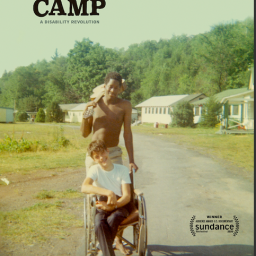 "Image Description: The poster for Crip Camp, which features a vintage image of two Jened campers, one standing behind the other's wheelchair with a summer camp scene in the background. At the top left corner of the image, black text reads: ""Crip Camp, a Disability Revolution."""