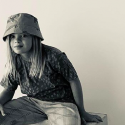 Image Description: Sofia Sanchez poses for a modeling shoot. She is seen in black and white. A bucket hat covers her long blond hair. She leans her right hand on her knee and offers a serious, cool look to the camera.
