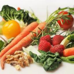 A photograph of fruits and vegetables: tomatoes, carrots, walnuts, bok choy, raspberries, and thyme.
