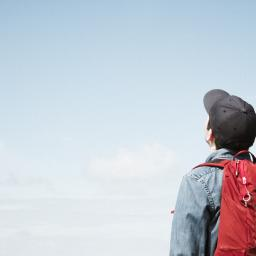 Student with backpack staring into the empty sky