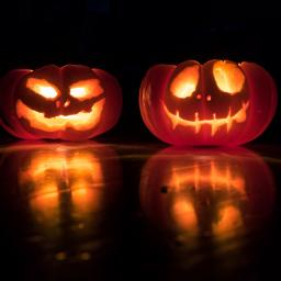 two carved pumpkins lit up. One with a goofy face and the other with a scarier more serious face.