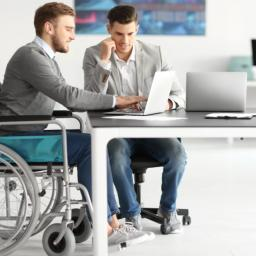 two men sitting at a table, one in a wheelchair, both working on a project