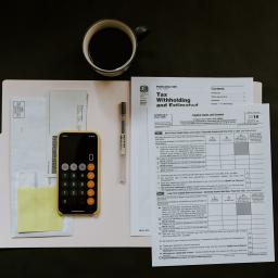Image Description: Bird's eye view of tax forms, a calculator, and a cup of coffee displayed on the top a desk.
