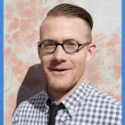 Image of man smiling at the camera. He is wearing a white and blue small checkered shirt and a blue tie. He is wearing glasses and his hair is parted to the side.