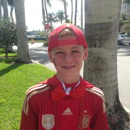 Image of young boy wearing all red. Smiling towards the camera. The scenery is of a tropical residential area and palm trees can be seen in the background. The boy is wearing a hat, face paint, a jacket, a bowtie, and beaded necklaces all in red.