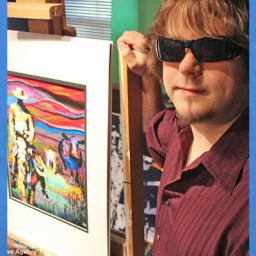 Image of man with black sunglasses. he has light brown shaggy hair and is wearing a maroon polo shirt unbuttoned. He is standing next to one of his paintings, which is on an easel in his workshop.