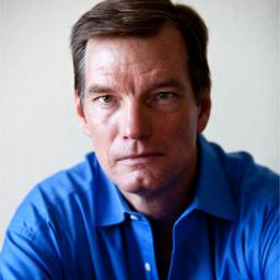 Image of John Quinn. He is wearing a blue shirt. His face has a determined look.